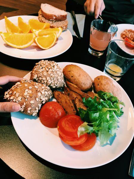 Panecillos, naranja, patatas, tomates y hojas de ensalada fresca.