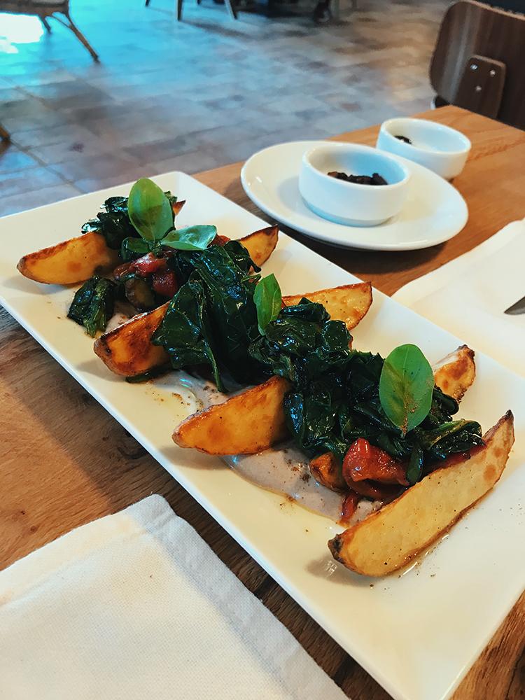 Patatas con pimientos, espinacas y mayonesa de ajo negro.